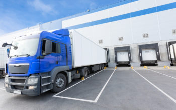 Big distribution warehouse with gates for loads and blue truck