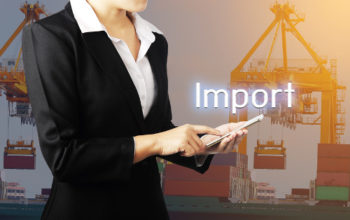 Businesswoman holding phone over container cargo freight ship with working crane bridge in shipyard background, Business industry logistic import export concept.
